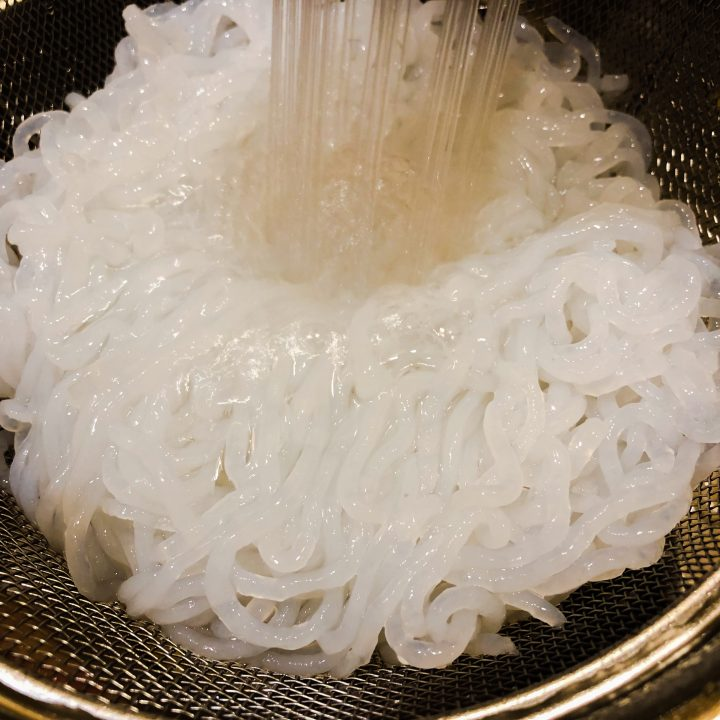 Shirataki-noodles-being-rinsed-in-a-strainer